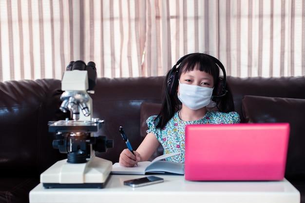 Maschera e cuffie d'uso della ragazza del piccolo bambino che imparano online usando computer portatile e microscopio a casa, istruzione a distanza