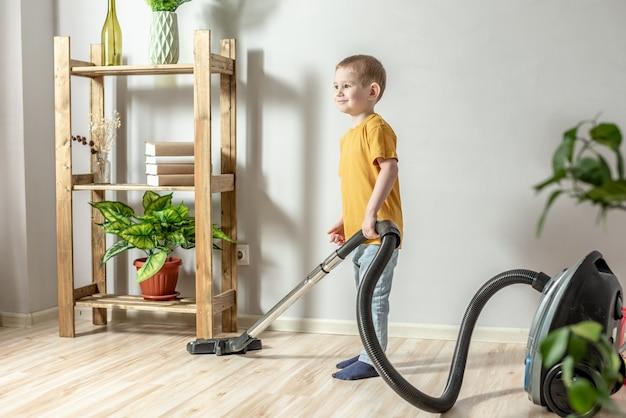 Un bambino aiuta i suoi genitori nelle faccende domestiche, pulisce il pavimento usando un aspirapolvere