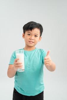 Piccolo bambino che tiene un bicchiere di latte