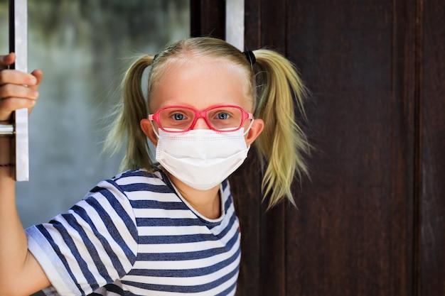 Piccolo bambino che guarda fuori porta aperta dopo essere rimasto a casa a causa di attività esterne vietate