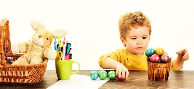 Piccolo bambino che dipinge le uova di pasqua. creatività pasquale per bambini. il ragazzo del bambino decora l'uovo di pasqua.