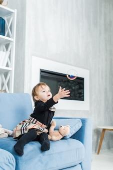 Piccolo bambino che gioca a casa con le bolle di sapone