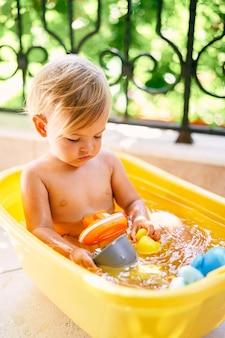 Piccolo bambino che gioca con i giocattoli seduto in una bacinella d'acqua