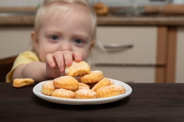 Il piccolo bambino raggiunge per il piatto dei biscotti. bambini e zucchero, cibo spazzatura.