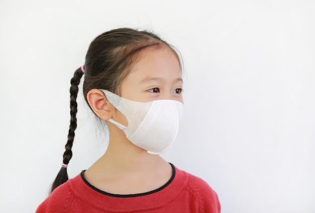 Il bambino piccolo indossa la maschera per il viso per proteggere il virus su bianco