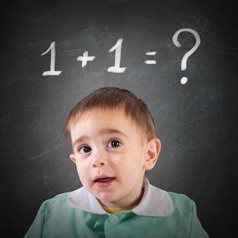Piccolo bambino con la lavagna con il calcolo di matematica