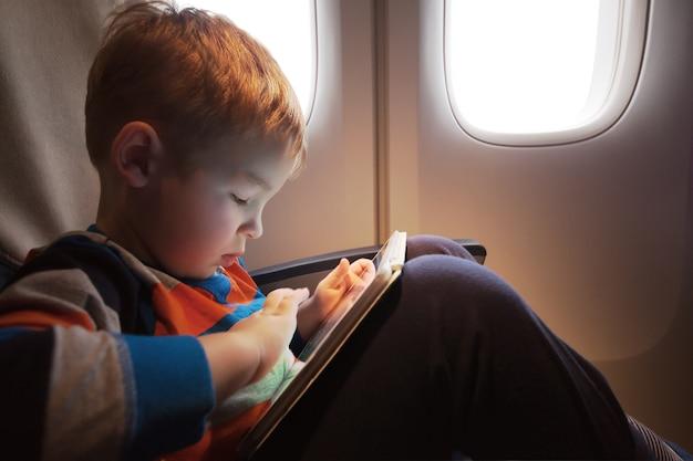 Piccolo bambino con computer tablet in grembo seduto dalla illuminatore nell'aereo