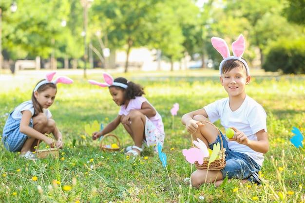 Bambini piccoli che raccolgono le uova di pasqua nel parco