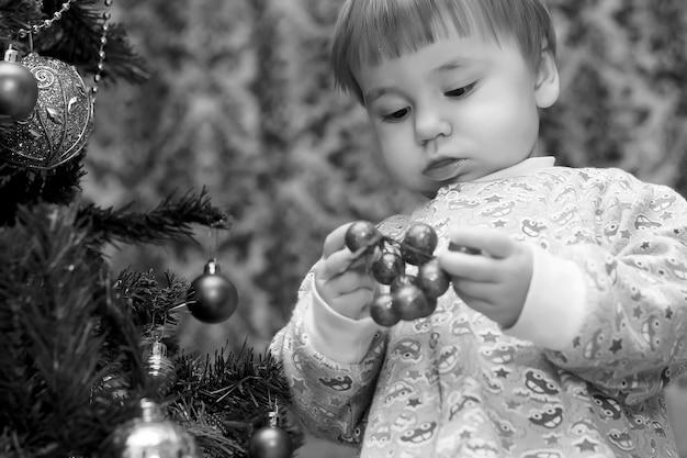 Bambini piccoli vicino a un albero di natale prima delle vacanze