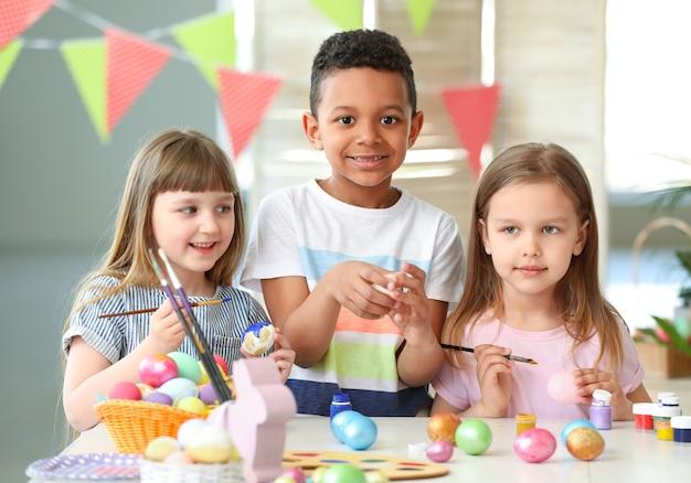 Piccoli bambini che dipingono le uova di pasqua a casa