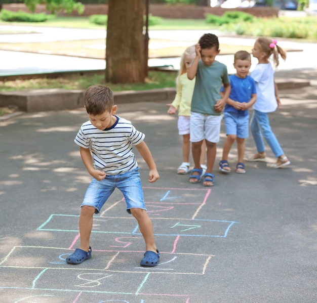 Bambini piccoli che giocano a campana, all'aperto
