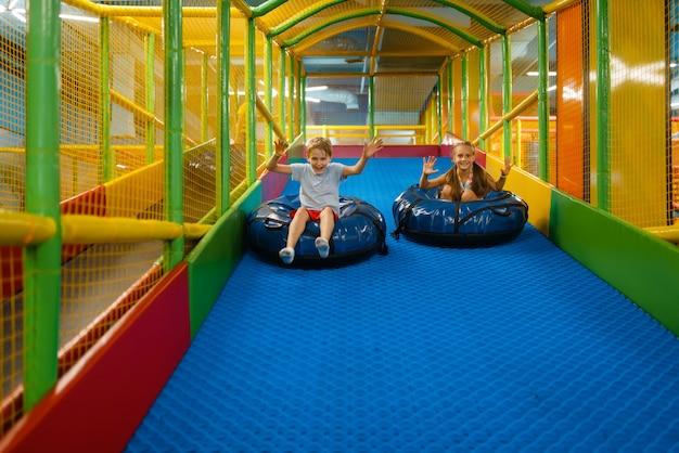 Piccoli bambini cavalcano su tubi, parco giochi nel centro di intrattenimento. area giochi interna, sala giochi