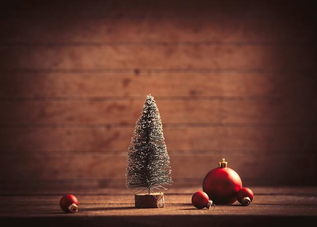 Piccolo albero di natale e bagattelle sulla tavola di legno e sullo sfondo