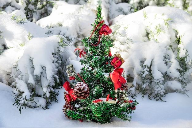 Piccolo albero di natale con giocattoli e coni in una foresta di neve