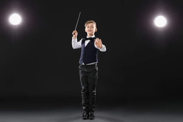 Piccolo direttore d'orchestra sul palco buio Foto Premium