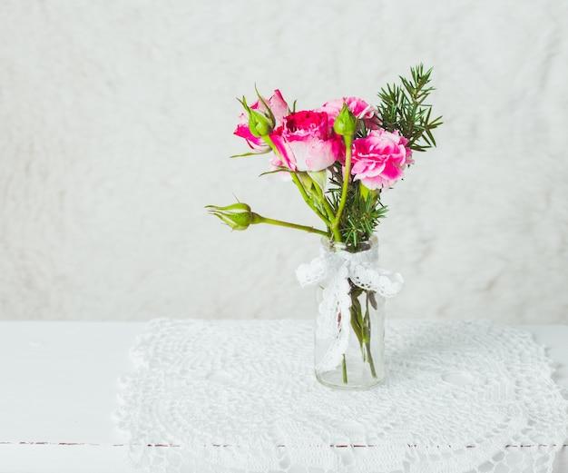 Piccolo bouquet accogliente in bottiglia di vetro su centrino all'uncinetto. stile vintage
