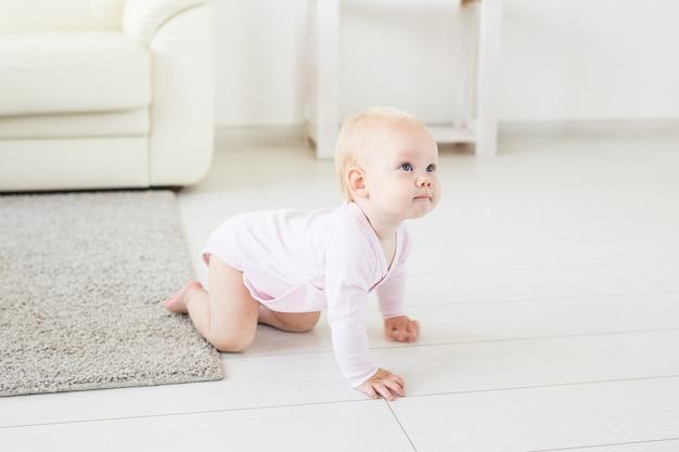 Piccola neonata strisciante di un anno che striscia sul pavimento in soggiorno luminoso e luminoso sorridente e