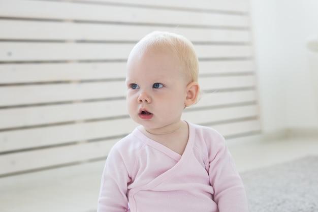 Piccola neonata gattona di un anno seduta sul pavimento in soggiorno luminoso e luminoso sorridente e