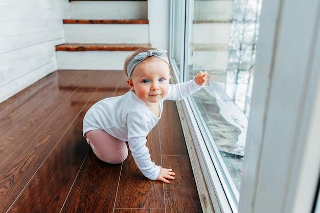 Piccola neonata strisciante ubicazione sul pavimento in soggiorno luminoso vicino alla finestra sorridente