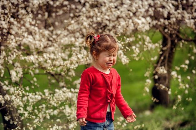 Piccola ragazza che piange in una giacca rossa triste e sconvolta su uno sfondo di albero in fiore