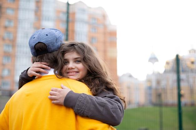 Piccola ragazza bruna riccia che abbraccia suo fratello maggiore durante il gioco nel cortile dello sport