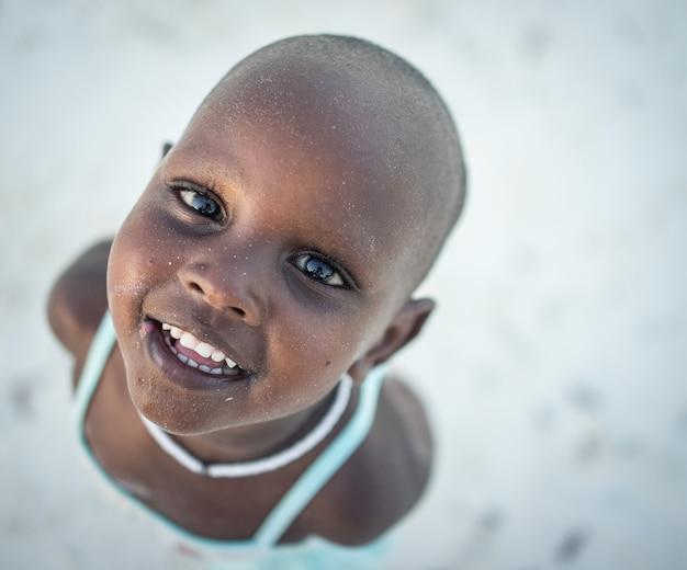 Piccola ragazza africana sveglia sulla spiaggia
