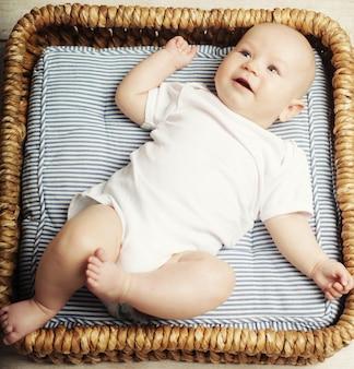 Piccolo bambino carino sdraiato nel cestino