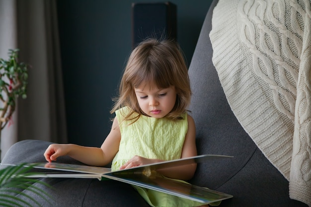 Piccola neonata sveglia in vestito giallo che legge un libro a casa