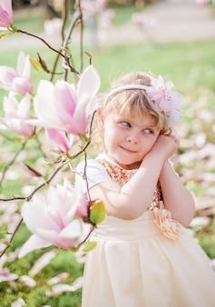 Piccola ragazza bionda carina di 3 anni gioca in un parco vicino a una magnolia in fiore.