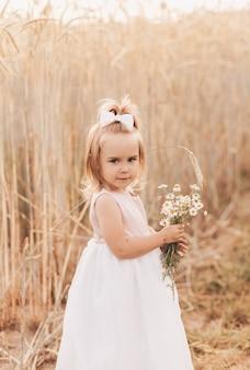 Piccola ragazza bionda carina con un mazzo di fiori di campo in natura in estate