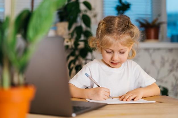 La piccola ragazza bionda carina scrive, studia a casa davanti a un laptop, impara online, torna a scuola.