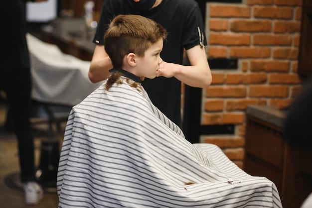 Un ragazzino carino siede in un parrucchiere dallo stilista, uno scolaro si fa tagliare i capelli in un salone di bellezza, un bambino da un barbiere, un taglio di capelli da uomo corto.