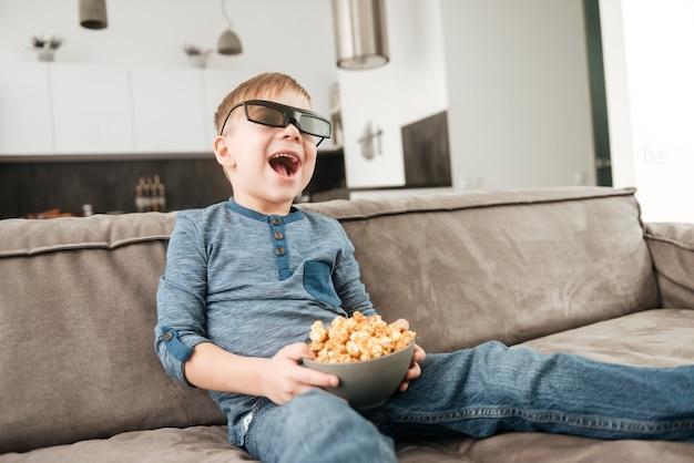 Ragazzino carino seduto sul divano a guardare la tv con occhiali 3d che tengono in mano i popcorn.