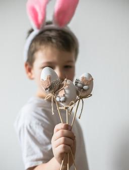Piccolo ragazzo sveglio che indossa le orecchie del coniglietto di pasqua, sorriso con le uova di pasqua
