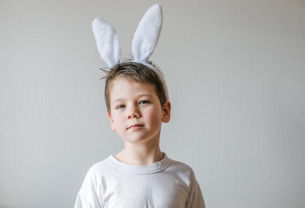 Piccolo ragazzo sveglio che indossa le orecchie del coniglietto di pasqua, sorriso