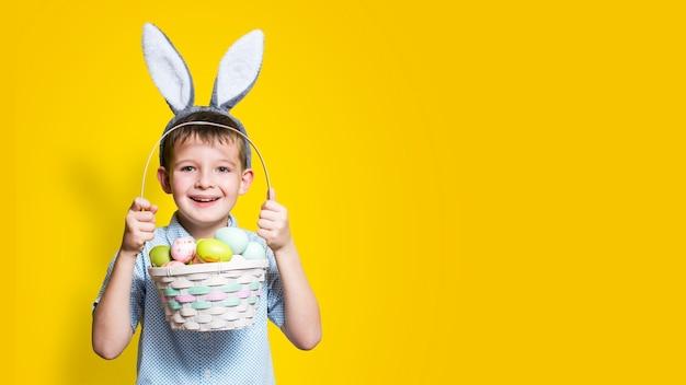 Piccolo ragazzo carino con un cesto di pasqua nelle sue mani e orecchie da coniglio in testa su uno sfondo giallo