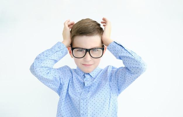 Piccolo ragazzo caucasico carino che indossa una t-shirt spogliata contro il muro bianco concentrandosi su un'idea con uno sguardo serio, pensando con entrambi gli indici che puntano alla fronte.
