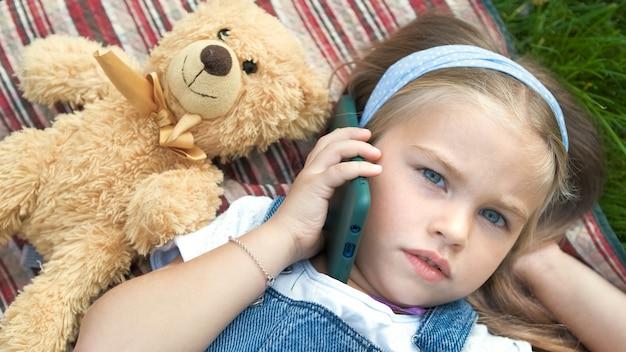 Bambina bambino carino posa su una coperta sul prato verde in estate all'aperto con il suo giocattolo orsacchiotto parlando al telefono cellulare.