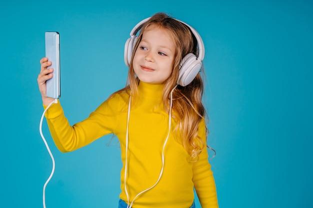 Una piccola ragazza carina bambino ascolta la musica su grandi cuffie e prendendo un selfie
