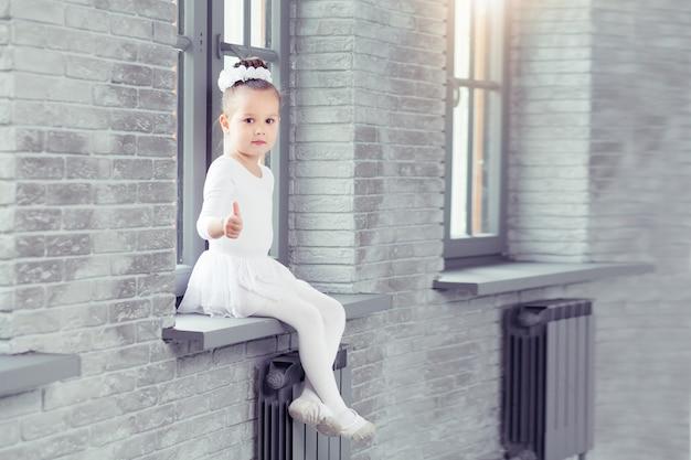 Bambina carina in forma di danza bianca seduta sulla finestra del moderno studio di danza