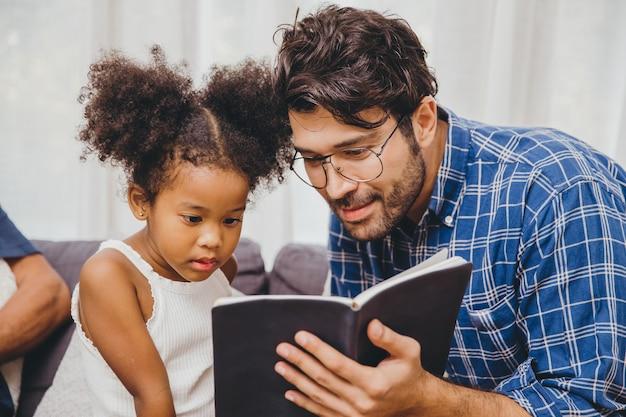 Piccolo bambino carino interessante il libro ama leggere e imparare il supporto da papà al concetto di bambino intelligente.