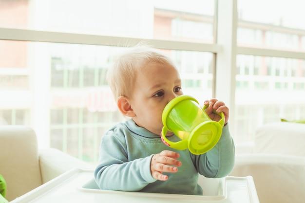 Piccolo bambino carino seduto su un seggiolone e beve dalla tazza verde per bambini