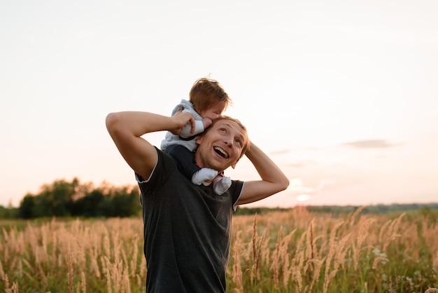 Una figlia carina si siede sul collo vicino a suo padre. padre e figlia stanno camminando nel campo