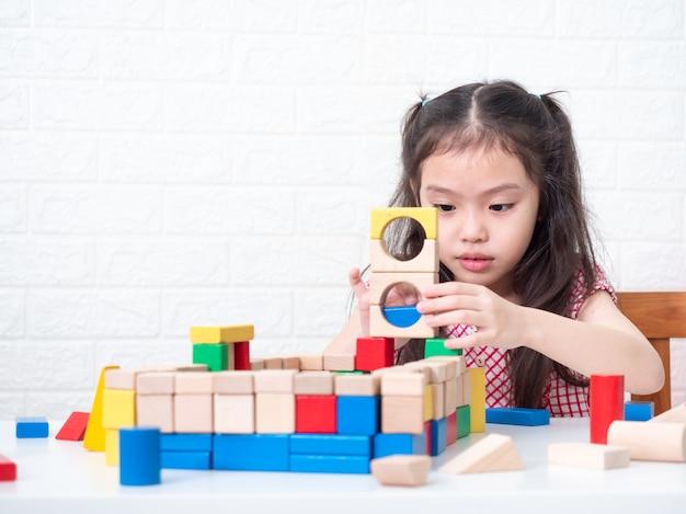 Bambina carina 6 anni giocando a blocchi di legno sul tavolo e muro di mattoni bianchi