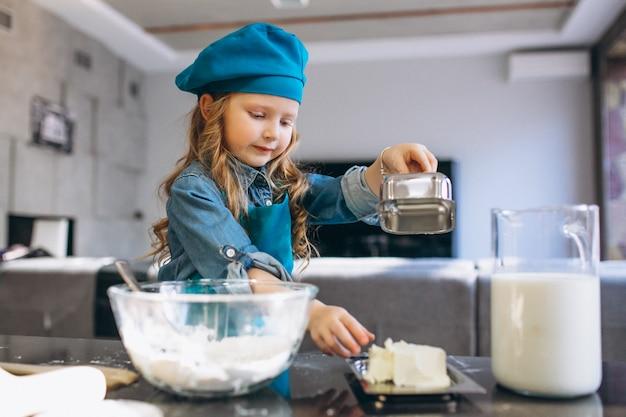 Piccola ragazza carina cottura in cucina