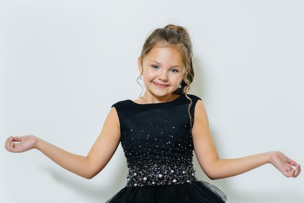 Una bambina carina in un vestito nero si siede e posa su un muro bianco