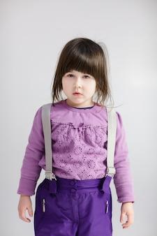 Piccola ragazza carina bruna in un maglione lavanda e pantaloni su sfondo grigio
