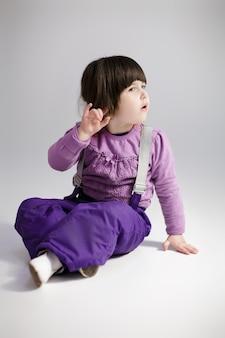 Piccola ragazza carina bruna in un maglione lavanda e pantaloni cercando di ascoltare su sfondo grigio