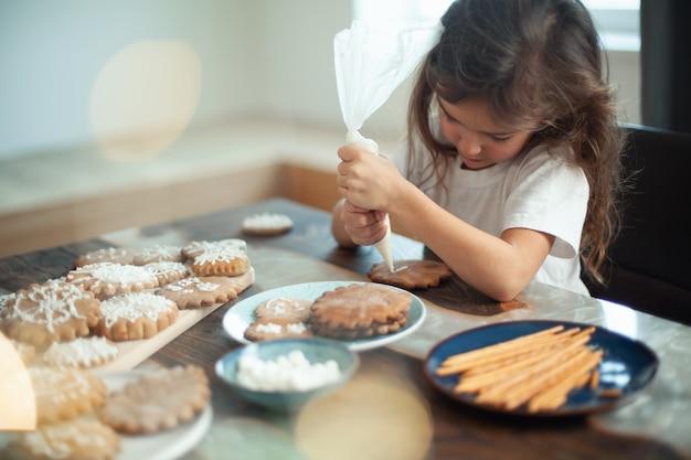 La bambina carina decora il pan di zenzero con la preparazione della glassa di zucchero per il concetto di natale
