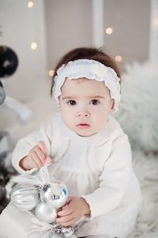 Piccola ragazza carina vestita come un angelo vicino all'albero di natale con regali per le vacanze di capodanno